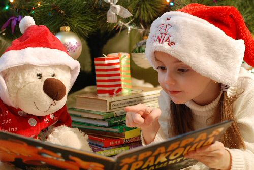 Girl ready Christmas book to teddy