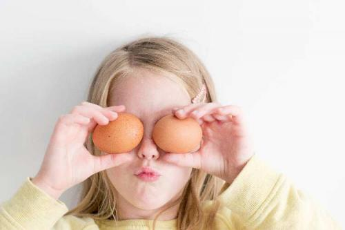 Girl holding eggs in front of her eyes